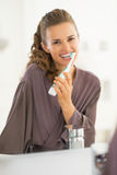 Happy young woman brushing teeth in bathroom Stock Photo