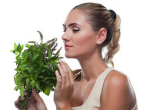 Happy young woman with with a bundle of fresh mint royalty free stock images