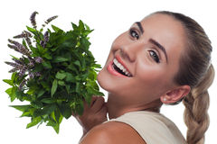 Happy young woman with with a bundle of fresh mint Royalty Free Stock Photos