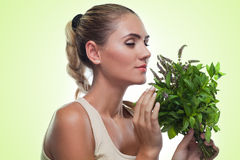 Happy young woman with a bundle of fresh mint. Concept vegetaria Stock Photos