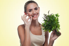 Happy young woman with a bundle of fresh mint. Concept vegetaria Royalty Free Stock Photos