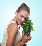Happy young woman with a bundle of fresh mint. Concept vegetaria Stock Photo