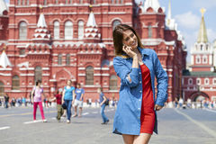 Happy young woman calling by phone in red square Royalty Free Stock Image