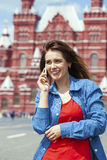 Happy young woman calling by phone in red square. Moscow, Russia Royalty Free Stock Photo