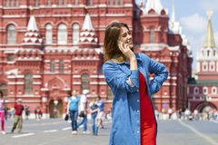 Happy young woman calling by phone in red square. Moscow, Russia Stock Photos