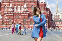 Happy young woman calling by phone in red square. Moscow, Russia Royalty Free Stock Images