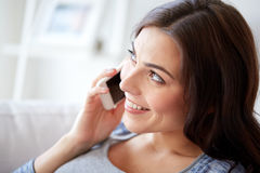 Happy young woman calling on smartphone at home Royalty Free Stock Photo