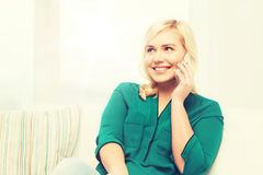 Happy young woman calling on smartphone at home Royalty Free Stock Photography