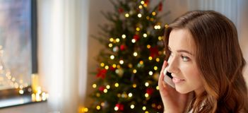 Happy young woman calling on smartphone at home stock photography