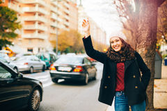 Happy young woman calling for a taxi in the city Stock Photography