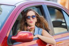 Happy young woman in car driving on the road. Royalty Free Stock Image