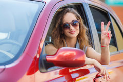 Happy young woman in car driving on the road. Stock Image
