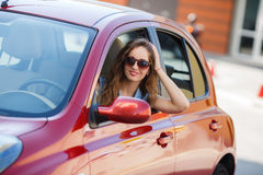 Happy young woman in car driving on the road. Stock Photo