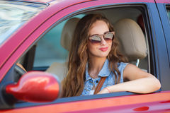 Happy young woman in car driving on the road. Stock Photography