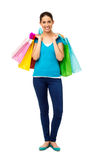 Happy Young Woman Carrying Shopping Bags. Full length portrait of happy young woman carrying shopping bags over white background. Vertical shot Stock Images