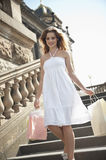 Happy young woman carrying shopping bags walking on staircase Stock Photography