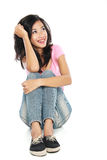 Happy young woman in casual wear sitting and thinking Royalty Free Stock Image