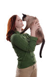 Happy young woman with cat. Happy young woman rubbing nose with siamese cat Royalty Free Stock Photos