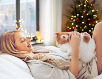 Happy young woman with cat in bed at home royalty free stock photos