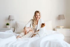 Happy young woman with cat in bed at home Royalty Free Stock Photography
