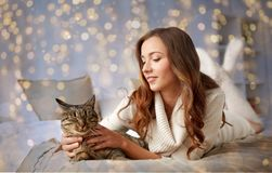 Happy young woman with cat lying in bed at home Royalty Free Stock Images