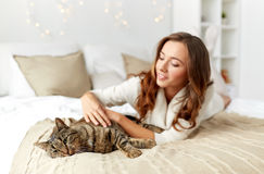 Happy young woman with cat lying in bed at home. Pets, comfort, christmas, winter and people concept - happy young woman with cat lying in bed at home stock images