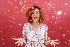 Happy young woman celebrating with confetti all around. Young woman throwing star shaped colorful confetti in air. Close up of woman in happy mood with confetti Royalty Free Stock Images