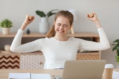 Happy young woman winner celebrating online win at home royalty free stock images