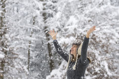 Happy young woman celebrating winter by raising her arms up in t Stock Photography