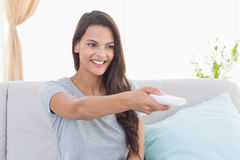 Happy young woman changing channels Stock Photography