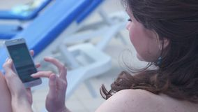 Happy young woman chatting on smart phone during rest at beach stock footage