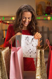 Happy young woman checking bags after christmas shopping Royalty Free Stock Images