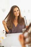 Happy young woman checking hair after straightening Royalty Free Stock Images