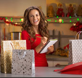 Happy young woman checking list of christmas presents Royalty Free Stock Photography