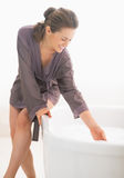 Happy young woman checking water temperature in bathtub Royalty Free Stock Photography
