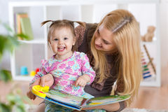 Happy young woman and child girl watching a baby booklet Royalty Free Stock Photography