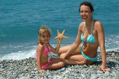 The happy young woman and child with starfish Royalty Free Stock Photos