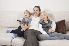 Happy young woman with children on sofa watching TV Royalty Free Stock Images