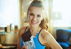 Happy young woman with chocolate bar in modern living room royalty free stock photo