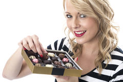 Happy Young Woman Choosing Chocolates to Eat Royalty Free Stock Photo