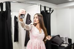 Young woman make a selfie in a new pink dress. Shopping clothes in mall or clothing store. Sale, fashion, consumerism. Happy young woman choosing clothes in mall stock photo