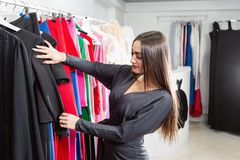 Happy young woman choosing clothes in mall or clothing store. Sale, fashion, consumerism concept.  stock images
