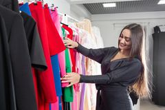 Happy young woman choosing clothes in mall or clothing store. Sale, fashion, consumerism concept.  stock photography