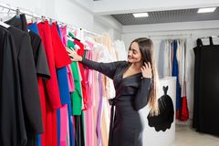 Happy young woman choosing clothes in mall or clothing store. Sale, fashion, consumerism concept.  royalty free stock images