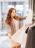 Happy young woman choosing clothes in mall. Sale, consumerism, shopping and people concept - happy young woman choosing clothes in mall Royalty Free Stock Photography