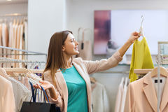 Happy young woman choosing clothes in mall Royalty Free Stock Image
