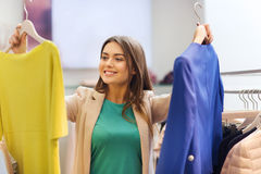 Happy young woman choosing clothes in mall Royalty Free Stock Images