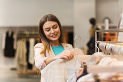 Happy young woman choosing clothes in mall Stock Image