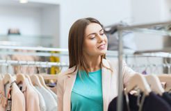 Happy young woman choosing clothes in mall Stock Photo