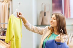 Happy young woman choosing clothes in mall Royalty Free Stock Photos